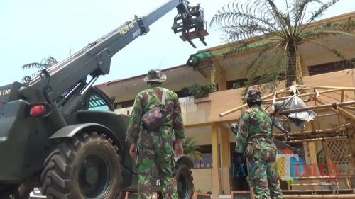 Petugas TNI saat melakukan pembersihan di di SDN Tulungrejo 03 Kota Batu, Selasa (22/10/2019). (Foto: Irsya Richa/MalangTIMES)