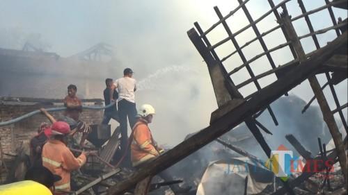 Damkar dan masyarakat berupaya memadamkan kobaran api.