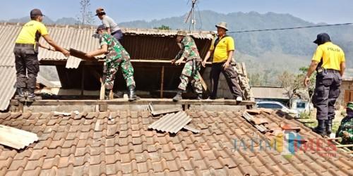 Gotong royong, petugas TNI dan Polisi membetulkan atas rumah warga di Desa Sumber Brantas,Kamis (24/1/02019).