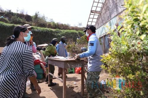 Warga gotong royong membersihkan rumah di Desa Sumber Brantas, Kecamatan Bumiaji.