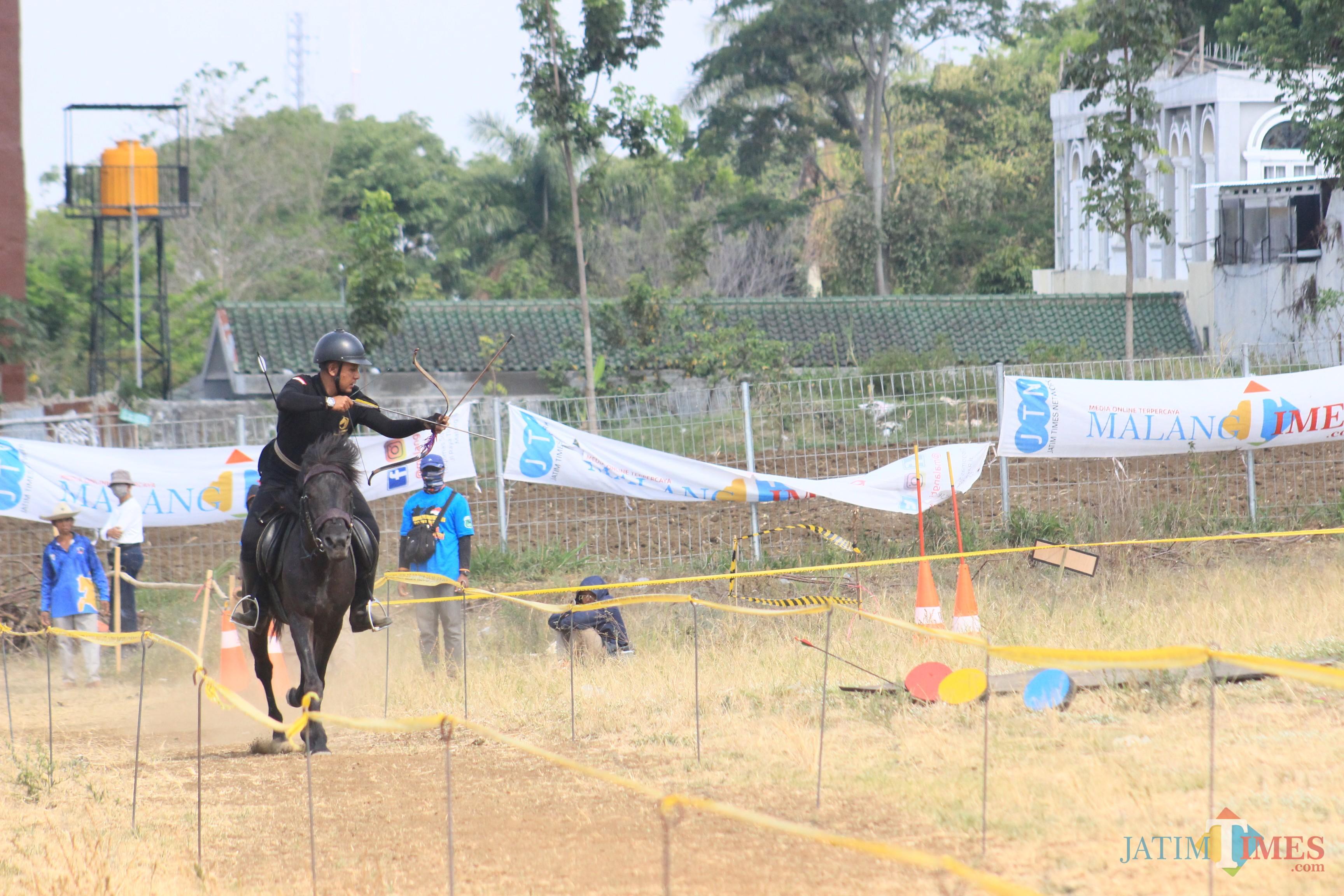 Salah satu peserta sedang beraksi memanah sambil berkuda dalam Turnamen Pemanah Berkuda Malang tahun 2019, Minggu (27/10/2019) di lapangan Paramount, Kota Batu. (Foto: Igoy/MalangTIMES)