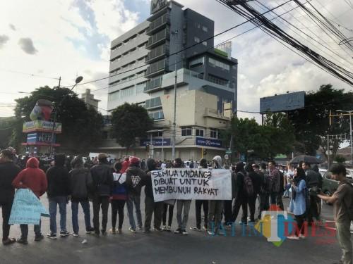 Suasana aksi puluhan massa Aliansi Malang Bergerak di kawasan Simpang Empat Rajabali, Kota Malang, Senin (28/10) (Arifina Cahyanti Firdausi/MalangTIMES)