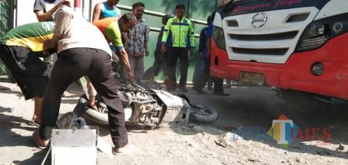 petugas saat mengevakuasi motor dari bawah bus (foto : Joko Pramono/Jatim Times)