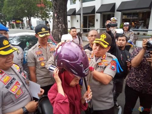 Kapolres Malang Kota, AKBP Dony Alexander saat memberikan helm kepada salah satu pengendara (Anggara Sudiongko/MalangTIMES)