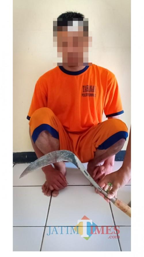 Tersangka Mochamad Roni beserta barang bukti sebilah celurit saat diamankan polisi. (Foto : Humas Polres Malang for MalangTIMES)