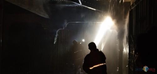 petugas saat memadamkan api di bengkel milik Budiono (foto : Joko Pramono/Jatim Times)