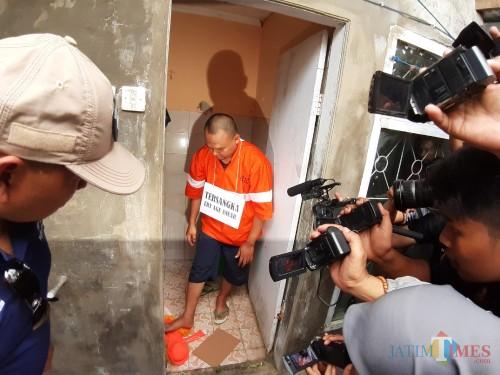 Salah satu adegan rekonstruksi pembunuhan saat pelaku menginjak tubuh korban di TKP, (Arifina Cahyanti Firdausi/MalangTIMES)