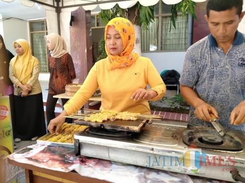 Salah satu peserta bazar saat mengolah ikan. (eko Arif s /JatimTimes)
