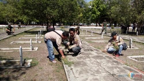 Jurnalis bersama dengan anggota kodim saat membersihkan taman makam pahlawan di Patrang,Jember. (foto : Moh. Ali Makrus / Jatim TIMES)