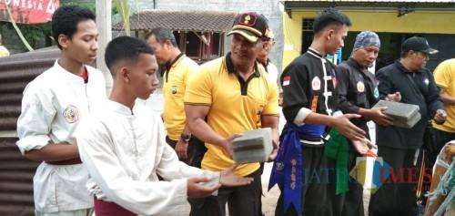 Kapolsek Kota, Kompol Rudi Purwanto mengangkut material bedah rumah bersama anggota perguruan silat (foto: Joko Pramono/ Jatim Times)