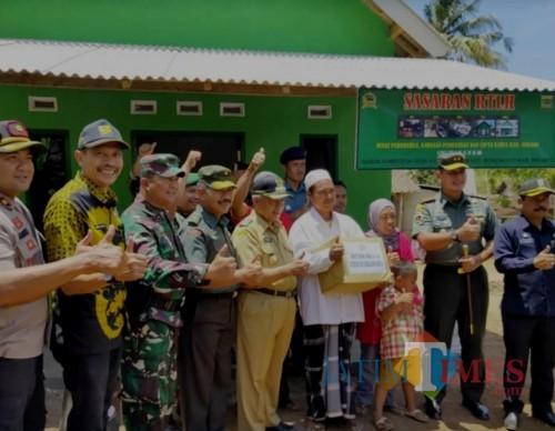 Kepala DPKPCK Kabupaten Malang Wahyu Hidayat (2 dari kiri) berpose di belakang salah satu rumah warga kurang mampu di Kedungsalam (DPKPCK for MalangTimes)