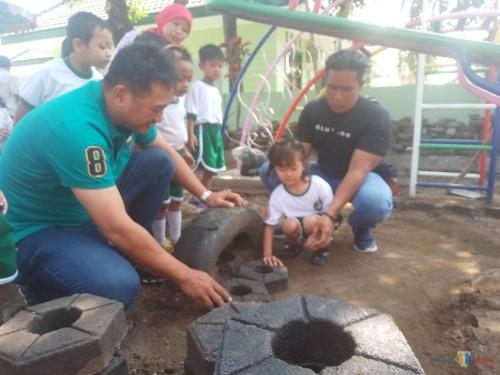 Kabid SDA Bambang Nugroho dan Pasi Intel Kodim 0833 Kapten Arh Imron bersama murid TK Kartika V 77 melakukan pemasangan paving secara simbolis. (Anggara Sudiongko/MalangTIMES)