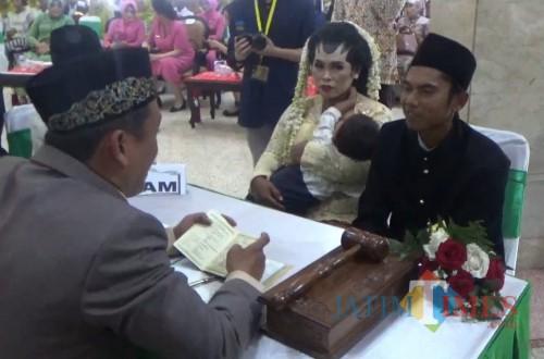 Salah satu pasangan pengantin yang mengikuti nikah masal saat prosesi akad nikah sambil menggendong anak (Arifina Cahyanti Firdausi/MalangTIMES)