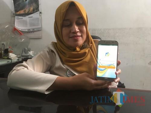 Kasubid Pembukuan dan Pelaporan Bapenda Kabupaten Malang, Nurul Hayati saat menunjukkan aplikasi Sipanji yang bisa di instal melalui smartphone android (Foto : Ashaq Lupito / MalangTIMES)