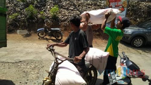 salah satu warga menebus pupuk bersubsidi yang baru datang (foto : Joko Pramono/Jatim Times)