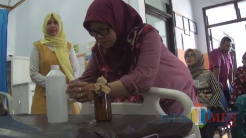 Petugas Dinkes Kabupaten Jombang terlihat memeriksa sampel air untuk masak yang diambil dari TKP. (Istimewa)