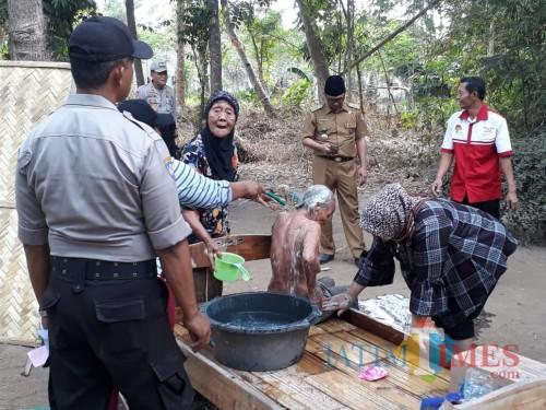 mbah Rupik saat dimandikan oleh tetangga dan staf desa (foto : Gito / Jatim TIMES)