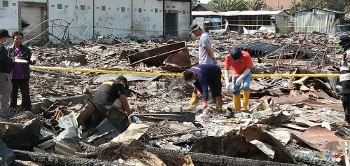tim Labfor Polda Jatim saat mencari penyebab kebakaran yang meratakan pasar Ngunut (foto : Joko Pramono/Jatim Times)