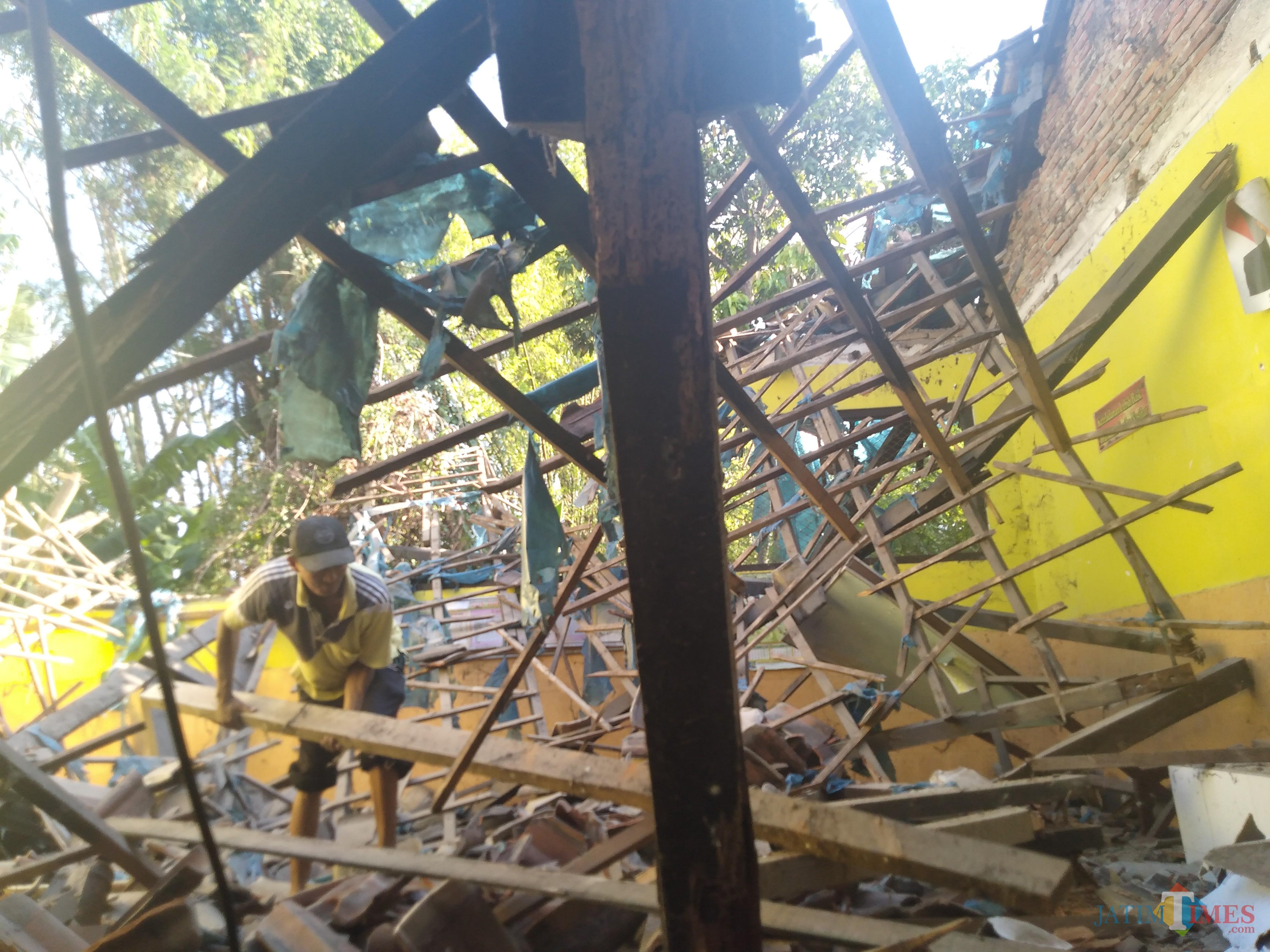 Pegawai SDN Dukuhklopo, Kecamatan Peterongan, Jombang terlihat membersihkan puing-puing runtuhan atap kelas. (Foto: Adi Rosul / JombangTIMES)