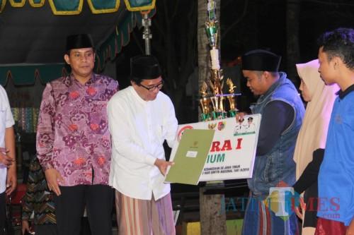 Wakil Bupati Jember Drs. KH. Abdul Muqit Arief saat menyerahkan piagam dan uang pembinaan kepada pemenang lomba (foto : izza / Jatim TIMES)