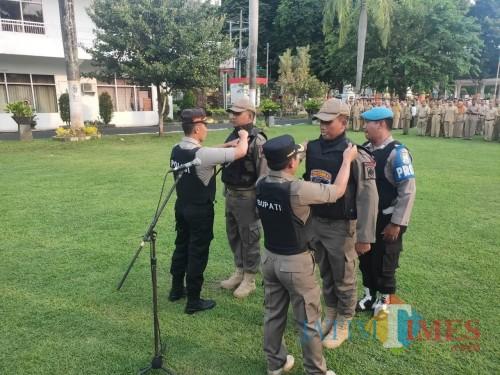 Dua anggota Satpol PP mendapakan atribut Tim Cobra dari Bupati dan Kapolres Lumajang (Foto : Moch. R. Abdul Fatah / Jatim TIMES)