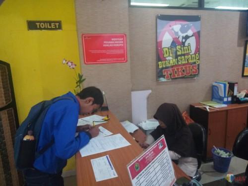 Petugas BP2D yang tengah melayani WP. Nampak tertempel di dinding Kantor BP2D, banner himbauan-himbauan anti korupsi (Anggara Sudiongko/MalangTIMES)