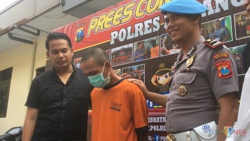 Tersangka MN (tengah) saat sesi rilis terkait aksi pencabulan terhadap anak kandung (Foto : Ashaq Lupito / MalangTIMES)