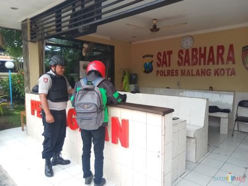 Petugas yang tengah berjaga ketat saat memeriksa salah satu pengunjung Polres Malang Kota (Anggara Sudiongko/MalangTIMES