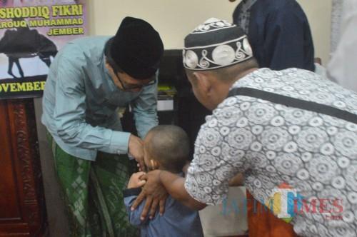 KH. Abdul Muqit Arief saat menyantuni anak yatim pada peringatan Maulid Nabi tadi malam (foto : Ali Makrus / Jatim TIMES)