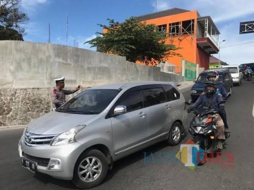 Petugas Polres Mojokerto saat mengondisikan jalur Pacet ke arah Kota Batu di area bundaran  taman Pacet, beberapa saat lalu. (Foto: istimewa)