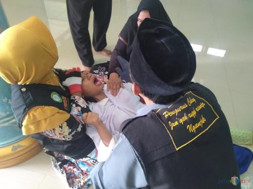 Proses Rukyah siswa kesurupan massal di SMPN 1 Perak, Jombang. (Foto: Adi Rosul / JombangTIMES)