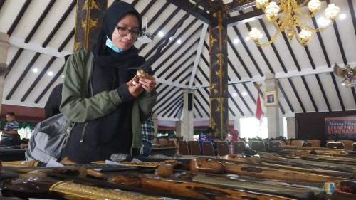 Pengunjung tengah melihat dan menikmati koleksi keris dalam Babad Pusaka Singhasari di Pendopo Kabupaten Malang (Pipit Anggraeni/MalangTIMES).