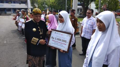 Bupati Malang HM. Sanusi (baju adat tradisional) saat memberikan apresiasi kepada para pelajar dalam  upacara peringatan Hari Jadi Ke-1259 Kabupaten Malang.