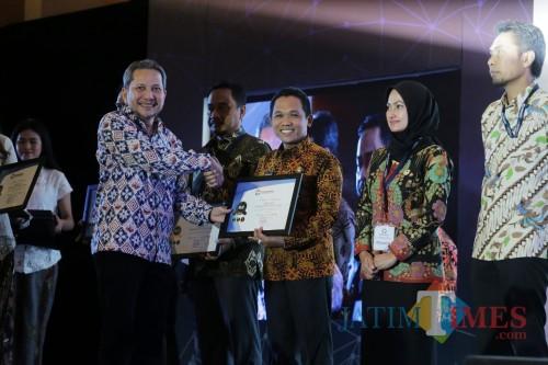 Bupati Lumajang H. Thoriqul Haq ketika menerima penghargaan dari Ombudsman (Foto: Moch. R. Abdul Fatah / JatimTIMES)