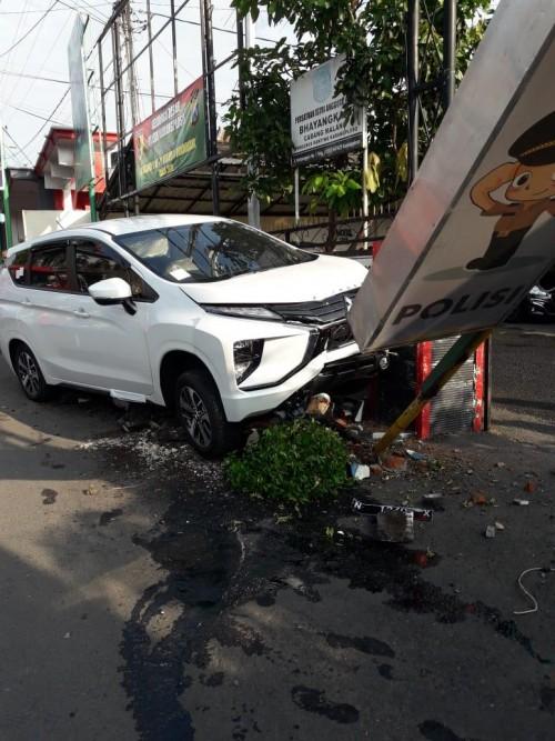 Kondisi mobil yang ringsek usai menghantam tiang neon box yang berada didepan kantor Polsek Karangploso (Foto : Istimewa)