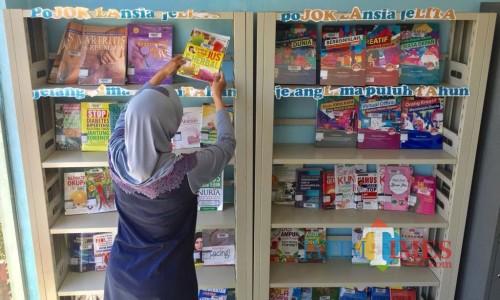 Salah satu pengunjung saat memilih buku di Taman Baca Masyarakat (TBM) Taman Bondas, Jl Sultan Agung, Kecamatan Batu. (Foto: Irsya Richa/MalangTIMES)