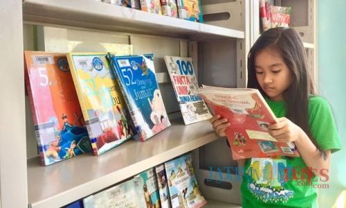 Salah satu anak sedang membaca buku di di Taman Baca Masyarakat (TBM) Taman Bondas, Jl Sultan Agung, Kecamatan Batu. (Foto: Irsya Richa/MalangTIMES)