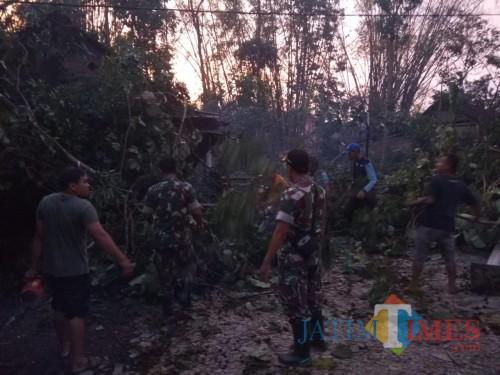 Petugas gabungan beserta warga saat berupaya mengevakuasi reruntuhan bangunan dan pepohonan setelah musibah angin kencang terjadi (Foto : Ashaq Lupito / MalangTIMES)