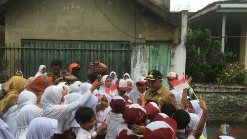 Ratusan siswa SD (Sekolah Dasar) yang ada di wilayah Kecamatan Poncokusumo saat menyambut dengan antusias kedatangan Bupati Malang HM Sanusi (baju coklat) (Foto : Ashaq Lupito / MalangTIMES)