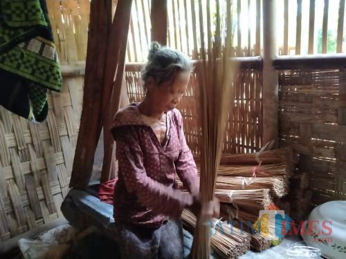 Mbah Sumirah saat membuat sapu lidi di rumahnya (foto : Gito / Jatim TIMES)