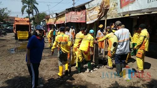 Kepala DLH Kota Malang, Rinawati saat memantau anggotanya membersihkan selokan di Pasar Blimbing (Hendra Saputra)