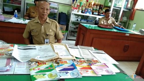 Wakasek Kesiwaan SMPN 2 Tulungagung tunjukan buku yang digunakan untuk Bimbel (foto : Joko Pramono/Jatim Times)