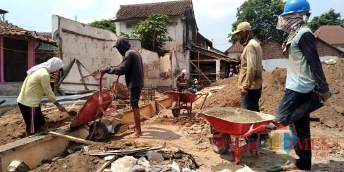 Pekerja saat membongkar kios Pasar Balung yang sedang dilakukan revitalisasi (foto: Minto/ JatimTIMES)