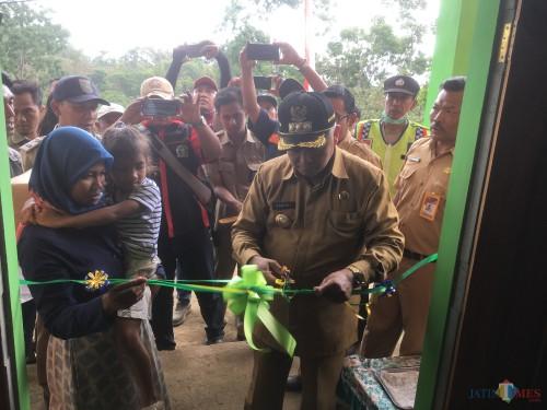 Bupati Malang HM. Sanusi (potong pita) saat meresmikan program bedah rumah yang direalisasikan  DPKPCK Kabupaten Malang (Foto : Ashaq Lupito / MalangTIMES)