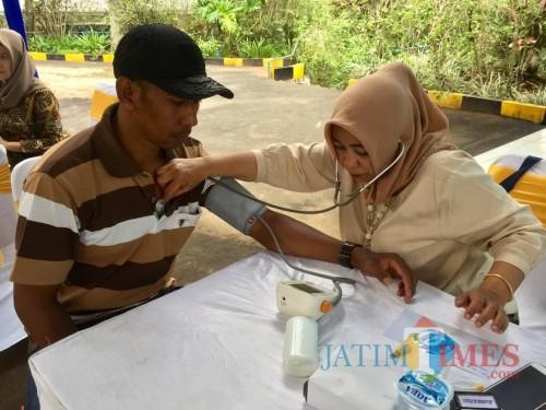 Salah satu warga saat ditensi tekanan darahnya oleh petugas di area Sumber Binangun, Desa Bumiaji, Kecamatan Bumiaji, Rabu (4/12/2019). (Foto: Irsya Richa/MalangTIMES)