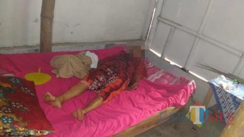 Korban saat pertama ditemukan tetangganya di tempat tidur dalam kondisi luka di leher. (foto : istimewa / Jatim TIMES)
