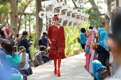 Seorang model nampak berjalan mengenakan busana tenun ikat Kediri dalam Gelaran Dhoho Street Fashion ke-5 di Hutan Joyoboyo Kota Kediri Jawa Timur, Kamis (05/12/2019) Pagi. (Foto: Bambang Setioko/JatimTIMES)