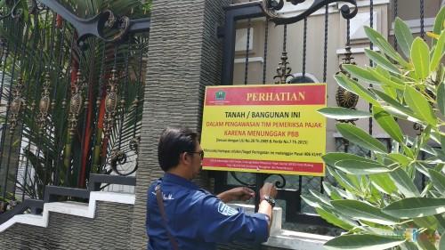 Pemasangan papan peringatan di rumah yang menunggak PBB oleh tim operasi gabungan BP2D Kota Malang. (Pipit Anggraeni/MalangTIMES).