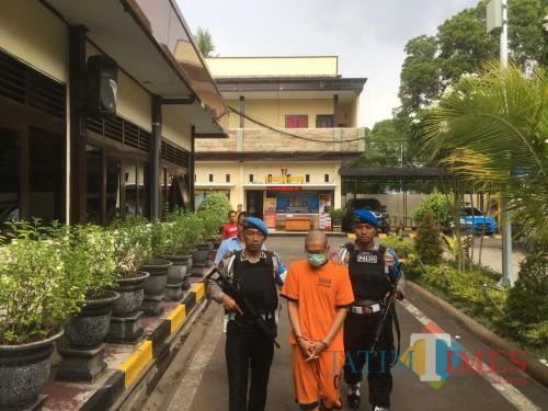 CH (tengah baju oranye) tersangka kasus pencabulan dan pemalsuan ijazah saat digelandang menuju ruang penyidikan Polres Malang (Foto : Ashaq Lupito / MalangTIMES)