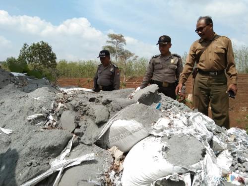 Anggota Polsek Kalangbret dan Pegawai Perhutani memeriksa tumpukan material yang diduga limbah B3 (foto: Joko Pramono/ JatimTIMES)
